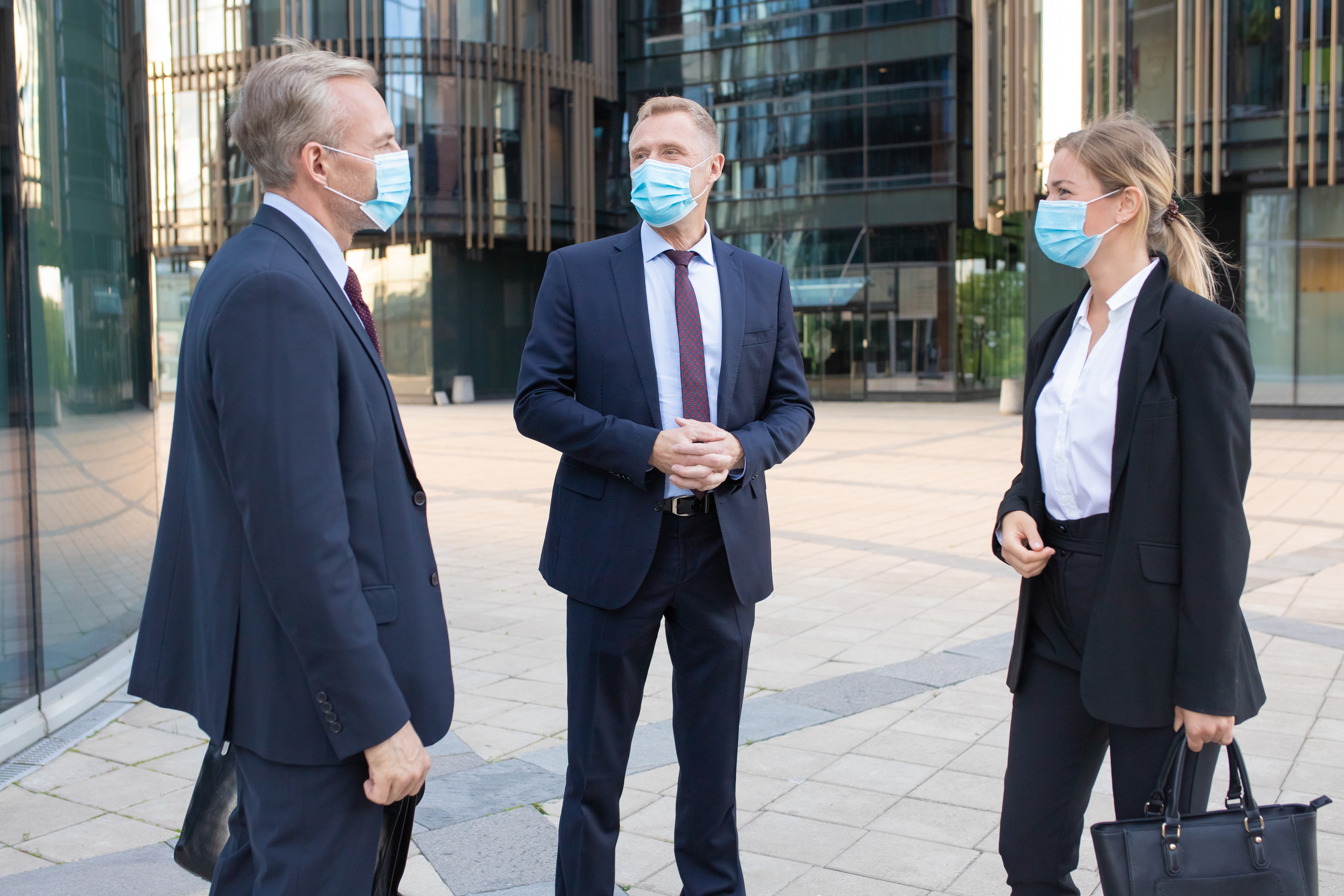 three-professional-business-colleagues-facial-masks-discussing-deal-outside-content-successful-managers-standing-street-talking-about-work-negotiation-protection-partnership-concept-1